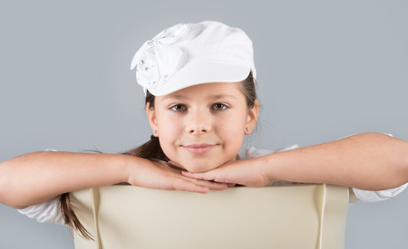 child model: Portrait of a smiling preteen girl in white cap sitting astride a chair