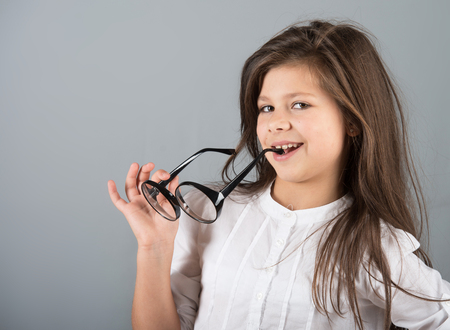 preteen model: Studio portrait of a preteen girl chewing on arms of glasses