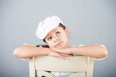 preteen model: Portrait of a preteen girl in white cap sitting astride a chair and dreaming