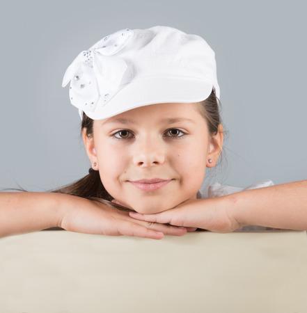 preteen model: Closeup portrait of a smiling preteen girl in white cap Stock Photo