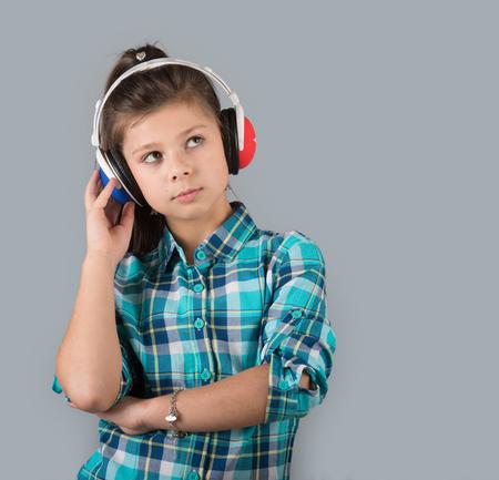 preteen model: Serious preteen girl in headphones looking away, studio shot, gray background
