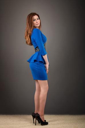 moda ropa: Retrato de cuerpo entero de una mujer en traje azul mirando a la cámara sobre fondo gris