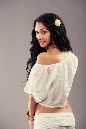 gypsy woman: Beautiful Gypsy girl looking back, gray background Stock Photo