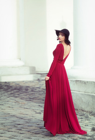 woman red dress: Woman in the long red dress looking back
