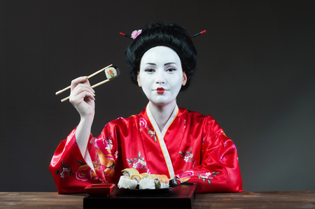sushi restaurant: Woman in geisha makeup eating sushi, gray background Stock Photo