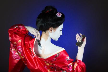 traditional costume: Girl applying geisha makeup, back view