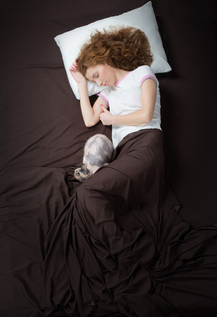 bed sheet: Sleeping girl and her cat, view from above Stock Photo