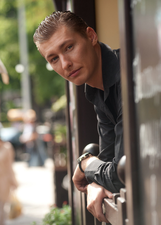man looking out: Portrait of young slavonic man looking out the window