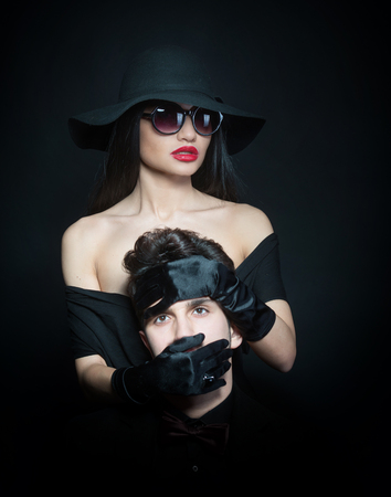 black satin: Woman covering the mouth of a man with her hands