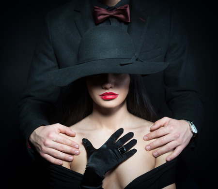 Portrait of a woman in big black hat and a man putting his arms on her shoulders Stock Photo