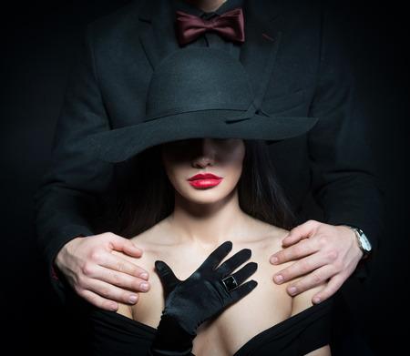 hombre con sombrero: Retrato de una mujer en gran sombrero negro y un hombre poniendo sus brazos sobre sus hombros Foto de archivo
