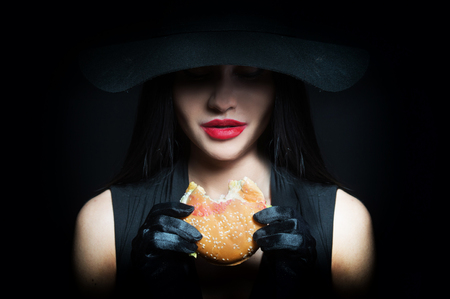 burgers: Woman in big black hat biting a hamburger