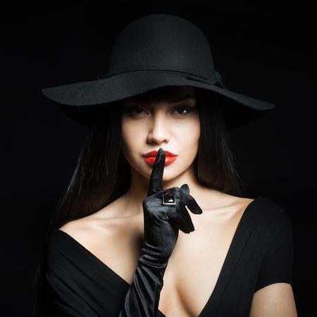 donne eleganti: Donna in grande cappello nero facendo un gesto di silenzio, ritratto in studio, sfondo scuro