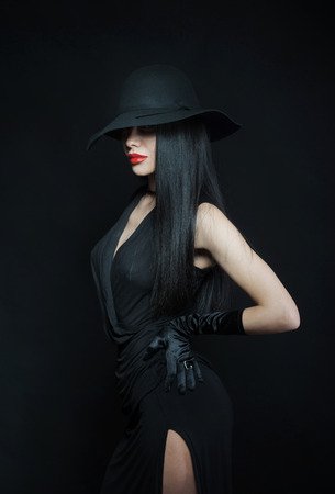 black hat: Woman in big black hat, studio portrait, dark background