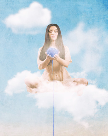 Angel with the thread of destiny sitting on the cloud Stock Photo