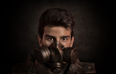 devastating: Portrait of soldier in chemical protection armor  and gas mask on dark background