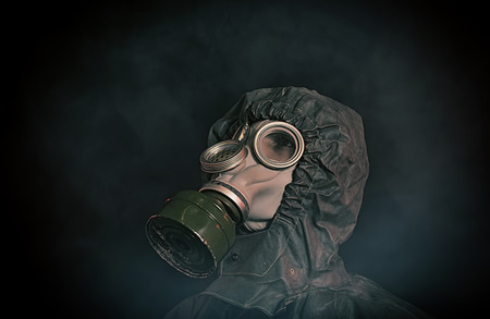 intimidate: Portrait of soldier in chemical protection armor and gas mask looking up