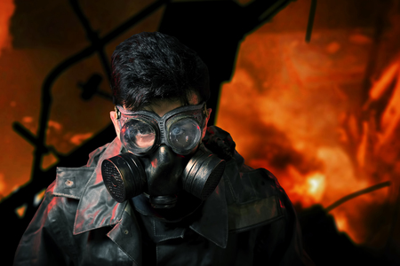devastating: yberpunk stalker soldier in chemical protection armor and googles with flames on background