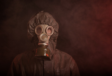 devastating: Portrait of soldier in chemical protection armor and gas mask with smoke in background Stock Photo