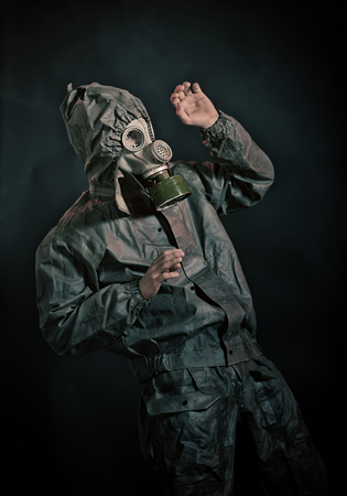 devastating: Soldier in chemical protection armor and gas mask defends himself with his hands Stock Photo