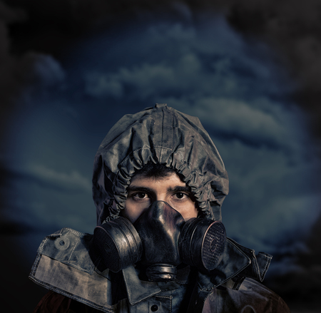 devastating: Portrait of a man in chemical protection armor and gas mask with stormy sky in background Stock Photo
