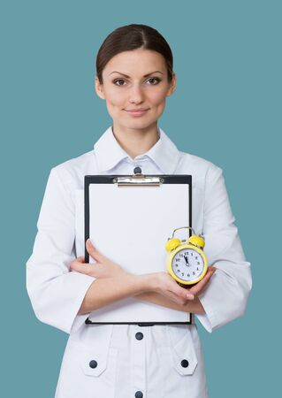 smock: Portrait of a smiling nurse with a clipboard and a clock