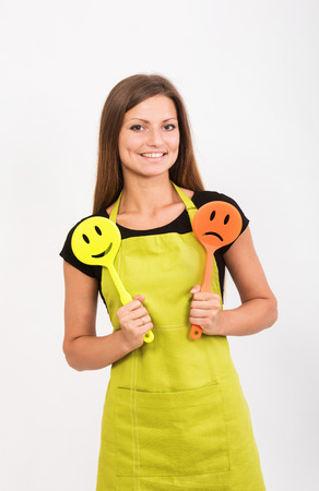 woman diet: Cheerful girl in yellow apron holding a smiley face spatula and a sad face spatula Stock Photo