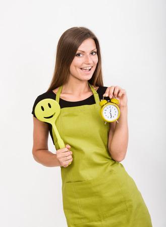 mandil: Niña alegre en delantal amarillo que sostiene una espátula de cara sonriente y un reloj despertador Foto de archivo