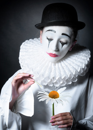 Sad mime Pierrot guessing on a daisy Stock Photo