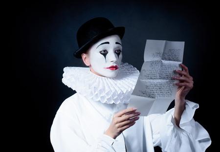 love letter: Triste Pierrot mimo leer la carta de amor Foto de archivo