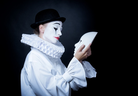 Sad mime Pierrot looking at the mask Stock Photo