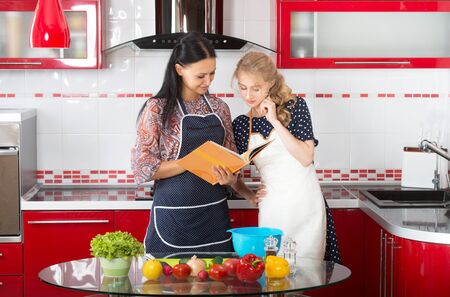 inexperienced: Two women in the kitchen cook using cookbook