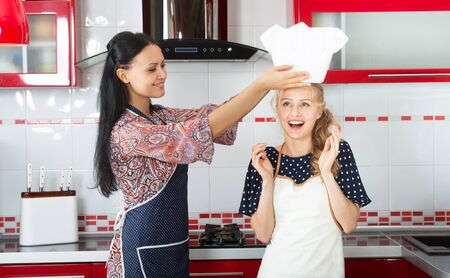 younger: Smiling woman putting a chef hat on her younger friends head