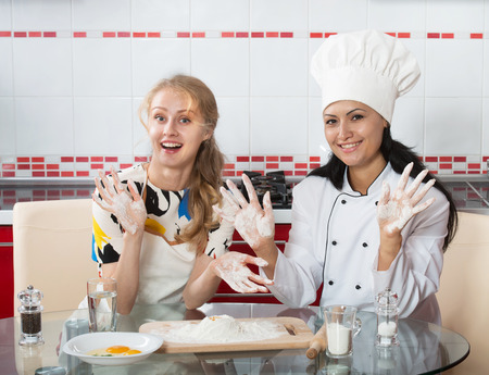 culinary skills: Woman in chef uniform explaining to her younger friend how to make dough Stock Photo