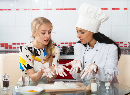 inexperienced: Woman in chef uniform explaining to her younger friend how to make dough Stock Photo