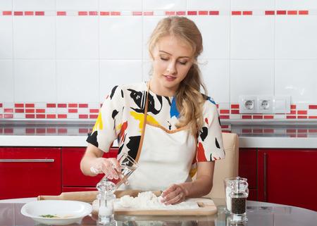blond girl: Smiling blond girl making dough