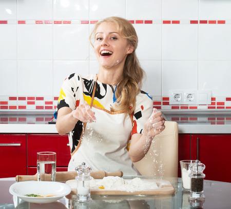 culinary skills: Smiling blond girl making dough