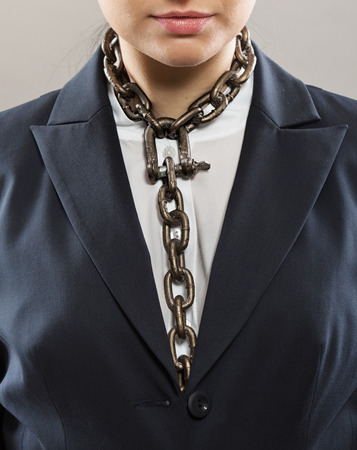 slave labor: Female office worker with chain tie, concept Stock Photo