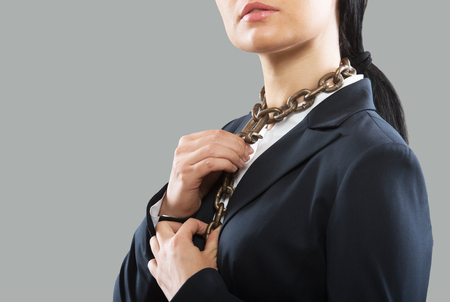 slave labor: Female office worker adjusting the neck chain tie, concept