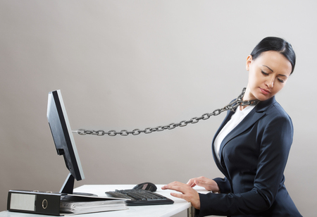 enchain: Female office worker chained to her computer