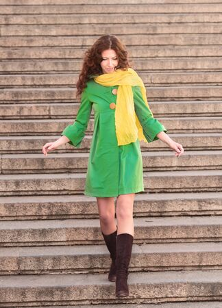 overcoat: Full-length portrait of a pretty woman in green overcoat descending stairs Stock Photo