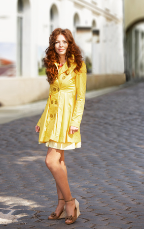 overcoat: Woman in yellow overcoat standing on the cobblestone road in sunny spring day Stock Photo