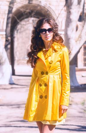 overcoat: Pretty woman in yellow overcoat and sunglasses