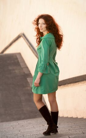 overcoat: Full-length portrait of a pretty woman in green overcoat descending stairs and looking back