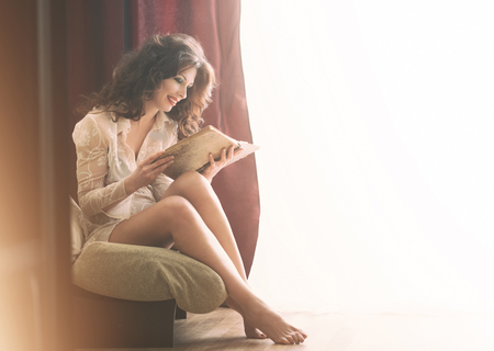 voluminous: Pretty girl relaxing with a book at home