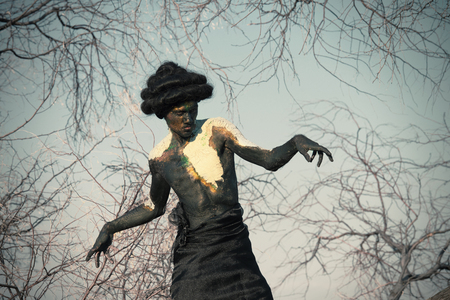 body paint: Earth spirit. Portrait of a guy in natural body paint with the trees branches
