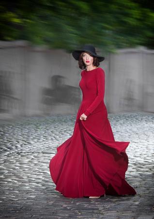 vestido de noche: Mujer en vestido de noche rojo que presenta en la calle Foto de archivo