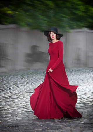 classy: Woman in red evening dress posing on the street