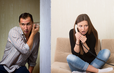 landline phone: Man with a glass listening to the girls phone conversation through the wall Stock Photo