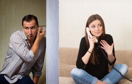 chismes: Hombre con un vaso de escuchar la conversaci�n telef�nica de la ni�a a trav�s de la pared Foto de archivo